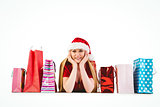 Festive blonde smiling at camera with gift bags