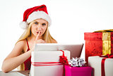 Festive blonde shopping online with laptop