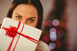 Pretty brunette holding christmas present