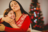 Festive mother and daughter hugging on couch
