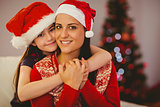 Festive mother and daughter smiling at camera