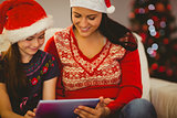 Festive mother and daughter using tablet