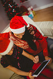 Festive mother and daughter using tablet pc