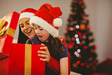 Festive mother and daughter opening a christmas gift