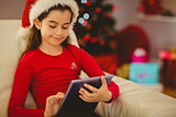 Festive little girl using tablet pc on couch