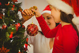 Mother and daughter hanging christmas decorations on tree