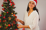 Woman hanging christmas decorations on tree