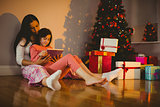 Mother and daughter using tablet beside the christmas tree