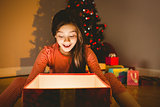 Little girl opening a glowing christmas gift