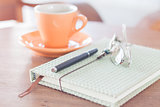 Notebook, pen and eyeglasses with orange coffee cup