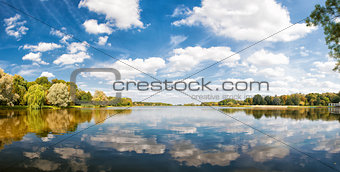 Autumn park, trees and blue sky reflected in water