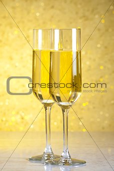 a pair of flutes of champagne on golden abstract background