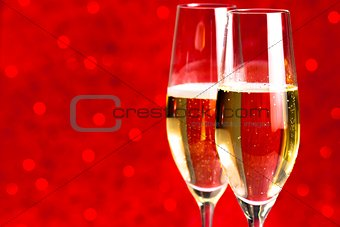 a pair of flutes of champagne red abstract background