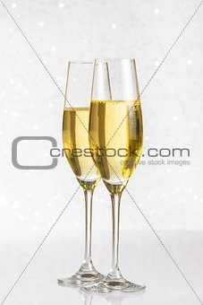 a pair of flutes of golden champagne on silver bokeh