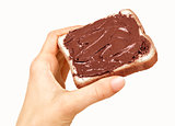baguette slice spread with nut-choco paste in man hand, isolated