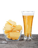 Glass of Fresh Beer and bowl of with Pile potato chips on a whit