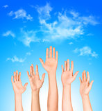 many open hands raised up against the sky,business concept