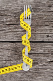 Fork and measuring tape on a thin wooden background