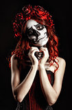 Young woman with calavera makeup (sugar skull) making heart sign