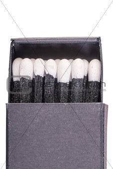Black matches in a box on a white background macro