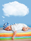 Yawning sleeping baby in funny hat with dream cloud for image or