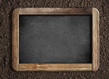 Blank chalkboard on soil background