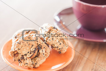 Closeup cereal cookies on orange plate and coffee cup
