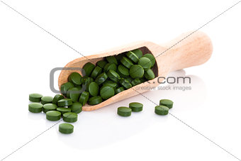 Green pills on wooden scoop.