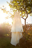 romantic wedding dress hanging from a tree