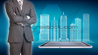 Businessman and wire-frame buildings on screen tablet