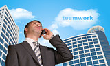 Businessman talking on the phone. Cloud with word teamwork
