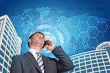 Businessman talking on the phone. Skyscrapers, sky and hexagons with world map