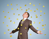 Businessman spread his arms. Gold stars fall from above