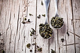two spoons of dried green tea leaves