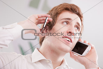 a guy telephoning with two mobiles
