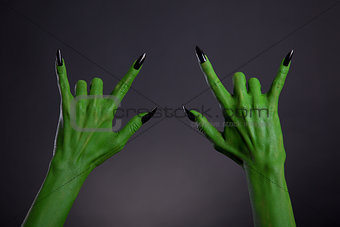 Green monster hands with black nails showing heavy metal gesture