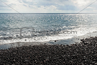 Black pebbles and sea