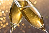 detail of a champagne flutes with golden bubbles on light bokeh background