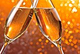 detail of champagne flutes on orange light bokeh background