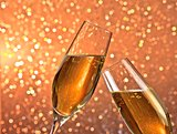pair of a champagne flutes with gold bubbles on light bokeh background
