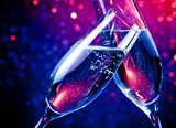champagne flutes with gold bubbles on blue tint light bokeh background