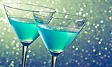 two glasses of blue cocktail on dark green tint light bokeh