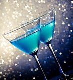 two glasses of blue cocktail on table