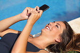 Girl texting on a smart phone on an hotel poolside on vacations
