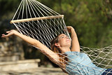 Happy woman relaxing on a hammock on holidays and raising arms