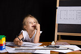 Girl-architect sitting behind a Desk and thought dreamily