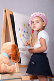 The girl in image of artist draws on easel