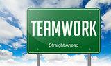Teamwork on Green Highway Signpost.