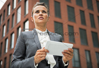 Portrait of serious business woman with tablet pc in front of of