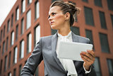 Serious business woman with tablet pc in front of office buildin